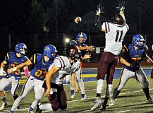 SETH GORDON  - Anthony Adams tries to sneak a pass past Tualatin defensive end Jared Ellison during Newberg's 48-13 home loss to the Timberwolves Friday night. The Tigers turned the ball over six times in the Three Rivers League matchup.