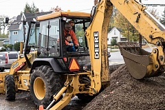 NEWS-TIMES PHOTOS: CHASE ALLGOOD - Greg Hollis of Forest Grove Puiblic Works shows Sidney Bates, 7, how to operate a backhoe Saturday, Oct. 15, at the Forest Grove Fire & Rescue Safety Fair.