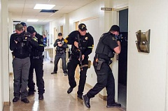 LINDA LARSON PHOTO - Law enforcement teams search room to room inside the old courthouse for the 'shooter' during the drill.