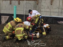 CONTRIBUTED PHOTO - Firefighters get ready to transport a man who was stuck at a construction site.