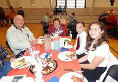 BARBARA SHERMAN - (From left) Robert Ramos, who was an 82nd Army Airborne paratrooper, and his wife Donna, enjoy the Sherwood Middle School veterans' breakfast with their grandchildren Elias and Elyana Ramos Russell.