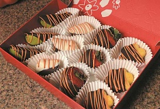 PAMPLIN MEDIA GROUP: VERN UYETAKE - For those who want to keep their centerpieces intact until the Thanksgiving meal begins, there are decorative fruit boxes. Filled with chocolate dipped fruit, each piece is drizzled with festive chocolate swizzle.