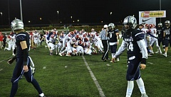 SPOKESMAN PHOTO: VERN UYETAKE - Wilsonville players walk off the field as Lebanon celebrates the victory.
