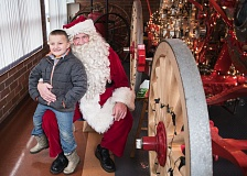 NEWS-TIMES PHOTO: CHASE ALLGOOD - Six year old Brodie Horstman poses for a photo on Santa's Lap during the annual Holiday in the Grove event in Forest Grove Saturday.