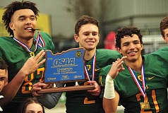 TIDINGS PHOTO: VERN UYETAKE - West Linn's (from Left) Keishon Dawkins, Tim Tawa and Qawi Ntsasa celebrate with the first-place trophy at the conclusion of their 62-7 win over Central Catholic in the Class 6A state championship game at Providence Park on Saturday.