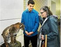 SETH GORDON - Newberg High School student Tristan Tuttle? shows off his senior project to a visitor at TigerCon April 22. Tuttle spent more than 40 hours constructing his taxidermied cat.