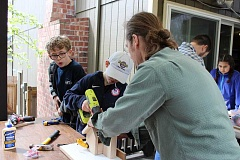 TIDINGS PHOTO: ANDREW KILSTROM - Teacher Daniel Sloan helps students drill holes for their bird houses.