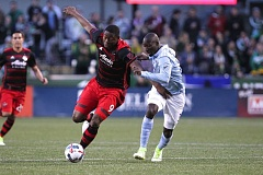 TRIBUNE PHOTO: JAIME VALDEZ - Portland Timbers forward Fanendo Adi (left) maneuvers around Sporting Kansas City defender Ike Opara in the first half of a game last Saturday at Providence Park.