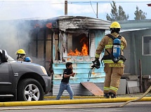 HOLLY M. GILL - A fire, which started in an unoccupied mobile home at Tops Trailer Park on Friday afternoon, spread to a second mobile home, occupied by a family of six, who weren't home at the time. Above, firefighter Aaron Marshall ensures that a young boy safely clears out of the area.
