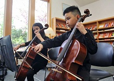 REVIEW PHOTO: KELSEY O'HALLORAN - Lake Oswego 8-year-olds Dannika and Andre Auduong play the cello during a Stafford Chamber Orchestra concert at the Wilsonville Public Library April 26.
