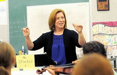 REVIEW FILE PHOTO - New teacher Kristi Stingle directs orchestra this September. She oversees Lakeridge Junior and Lakeridge High orchestras. She led Lakeridge to a Three Rivers League victory recently, and her high school wind ensemble will head ot state in May.