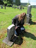 PHOTO BY ELLEN SPITALERI - Yvonne Weninger, treasurer of the Redland Pioneer Cemetery Board, looks at the grave of Spanish-American War veteran William Corry Hicinbothem who died in 1937.