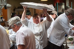 OUTLOOK PHOTO: JOSH KULLA - McMenamins employee Nancy Spangler carries a tray of bread through the crowded kitchen at the Black Rabbit Restaurant at Edgefield resort in Troutdale. The brewing giant is gearing up for the busy summer season, when it boosts its employee numbers. But with unemployment rates at all-time lows, it's getting harder for companies to find qualified workers.