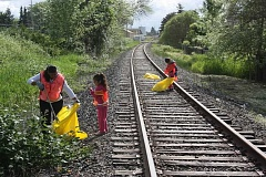 NEWS-TIMES FILE PHOTO - A mom and her two children help clean up the railroad corridor running through Cornelius during a previous Take Care of Cornelius Day cleanup drive.