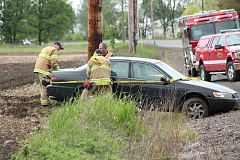 PIONEER PHOTO: CONNER WILLIAMS  - Crews from the Molalla Fire District rope off a vehicle that appeared to have left Highway 211 and then became stuck in a ditch just before the Meadowbrook bridge.