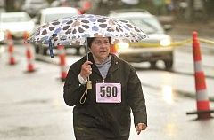 REVIEW PHOTO: VERN UYETAKE - An umbrella apparently didn't slow Elaine Rademacher down on Saturday. The Lake Oswego woman finished fifth in her age group in the Lake Run's 5K race.