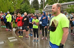 STAFF PHOTOS: VERN UYETAKE - Runners stand at attention as the National Anthem is played before the start of the 10k race.
