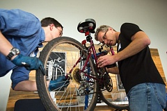 OUTLOOK PHOTO: JOSH KULLA - Joel Wagstaff and Joe Lagerstrom, volunteers from Gresham, help repair a bicycle last Thursday, May 18, at the repair cafe held at the Pathways Church, 3848 N.E. Division St., in east Gresham.