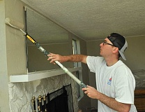 TIDINGS PHOTOS: VERN UYETAKE - Chad Bumgarner of Portland rolls out paint in the livingroom.