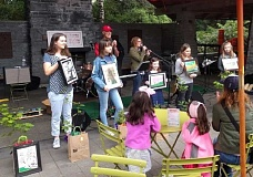 REVIEW PHOTO: ANTHONY MACUK - Winners (from left) Julia Yazhari, Sydney Leveque, Mila Kaplan, Jane Dakin and Natalie Kay stand with their framed artwork at the Farmers Market. Behind them, Mayor Kent Studebaker and Arborist Morgan Holen announce the prizes. Not pictured: William Thistle Thwaite, who won third place in the middle school division.
