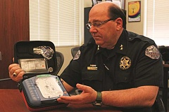 PHIL HAWKINS - Woodburn Police Chief Jim Ferraris displays an Automated External Defibrillator. Woodburn Proud is working with the WPD raise $10,000 to equip the department's entire fleet of vehicles with AEDs.