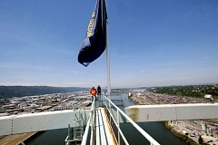 TRIBUNE FILE PHOTO - State crews must climb for nearly 20 minutes through an archway to raise and lower flags atop the Fremont Bridge. ODOT reported that concerns about asbestos will prevent workers from lowering flags for the Memorial Day holiday.