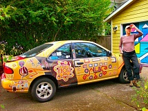 RITA A. LEONARD - Artist and ex-teacher Gaia Swan stands by her Aboriginal Art Car - as well as the colorful garage that she also painted.