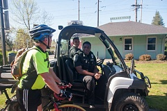 OUTLOOK PHOTO: JOSH KULLA - Bicyclist Kevin VanDyke of Wilsonville chats with Gresham police officers Kevin Carlson, left, and Gabriel Sey as they patrol the Springwater Trail. The city started police patrols in March but will transition to private security patrols this week.