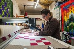 OUTLOOK PHOTO: JOSH KULLA - Marie Anderson's new quilting business in downtown Gresham features a high-tech quilting arm she uses to fashion elaborate wall art, bed coverings and more.
