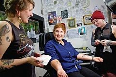 TRIBUNE PHOTO: JAIME VALDEZ - Portland State University grad student Arianna Warner reacts after having temporary tattoos placed on her forearms by Hawthorne Ink tattoo artists Aubrey Hight, left, and Kimber Teatro.