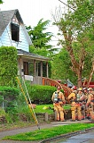 DAVID F. ASHTON - Fire crews pull a hose in through the front door, and quickly extinguish the second-story blaze, its cause apparently smoking-related.