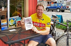 RITA A. LEONARD - Sellwood resident, and frequent author, Joe Kurmaskie displays some of his biking books in front of The Blue Kangaroo coffee shop on S.E. 13th in Sellwood.
