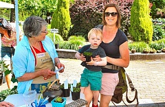 DAVID F. ASHTON - Eastmoreland Garden Club member Susan Hoover checks out sale customer Annie Radecki, who is holding young Alex.