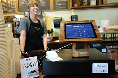 TRIBUNE PHOTO: JOSEPH GALLIVAN  - A barista at Sisters Coffee in the Pearl stands behind Squares white Contactless and Chip Card Reader. Customers can still swipe their credit card on the left edge of the iPad, but they can now also insert a credit card with a chip into the back of the white box, or tap it with their NFC-enabled phone and use Apple Pay or another contactless payment method.Square is targeting Portland for its thriving small business scene and becasue uptake of the new reader has been strong since its launch in fall 2015.