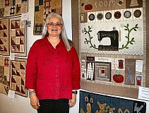 RITA A. LEONARD - Quilt designer & teacher Jolyn Buhl stands amidst a variety of quilts at the Woodstock Quilt Show.