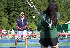 TIMES PHOTO: MILES VANCE - U.S. Davis Cup Team member John Isner hits balls with Abby Samkutty of Portland during the USTA Family Fun Fair at Tualatin Hills Tennis Center on Monday.