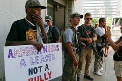 TRIBUNE PHOTO: JOHN RUDOFF - A concerned-appearing man holds an anti-Trump sign while standing next to a few heavily-armed members of the 'West Ohio Minutemen.' About 10 Minutemen paraded through the Public Square area carrying assault rifles.