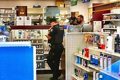 PHOTO BY DAVID F. ASHTON - Inside Brooklyn Pharmacy, officers interview the robbery victim as they begin their investigation.