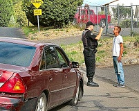 DAVID F. ASHTON - A Traffic Division officer performs a Field Sobriety Evaluation on the driver of a Toyota, badly damaged in the Brentwood-Darlington neighborhood by a poor turn that smashed the car into a curb and damaged a wheel.