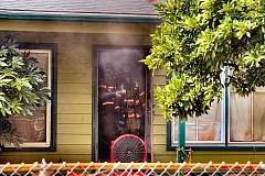 DAVID F. ASHTON  - Firefighters make their way out of the Nehalem Street house - the fire out, but the home still filled with smoke.