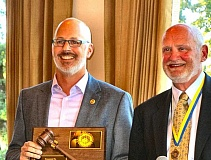 (Image is Clickable Link) ERIC NORBERG - The changing of the guard at Southeast Portland Rotary: Outgoing Club President Mark Pennington, left, is honored with a plaque by his successor, Joel Fields.