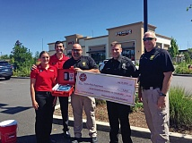 SUBMITTED PHOTO - Firehouse Subs presented a check to the Tualatin Police Department to fund the purchase of five automatic external defibrillators that are now installed in each patrol car in the city.