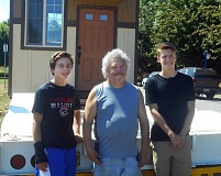 FOR THE TIMES: PHIL FAVORITE - Oregon Episcopal School student Jack Morisette (left) and older brother Henry Morissette join Ray Broddus (center) after the Morrisettes delivered the tiny house they built to Broddus at Dignity Village in Portland on Friday.