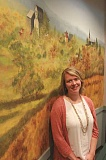 LINDSAY KEEFER - Katie Voss stands beside a mural of Mount Angel at St. Mary's Public Elementary School. Voss, who has served as a fifth-grade teacher at the school for a number of years, was recently hired to be the school's new principal, replacing Jennifer Christian who resigned in June.