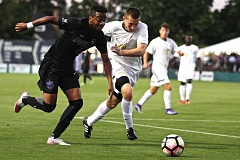 TRIBUNE PHOTO: JAIME VALDEZ - Portland Pilots forward Malcom Dixon (left) dribbles the ball upfield against  Wright State midfielder Eric Hutton at Merlo Field during Friday night's season opener for the UP men.
