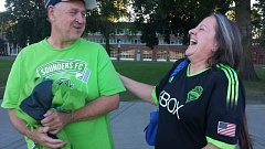 TRIBUNE PHOTO: JOSEPH GALLIVAN - Seattle Sounders fans Bob (no last name given) and Tammy Comery walk in Tom McCall Waterfront Park on Sunday after their team's 4-2 defeat by the Portland Timbers at Providence Park.