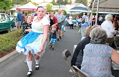 TIDINGS PHOTO: LESLIE PUGMIRE HOLE - Madeline Baumann, member of the Alpine Echoes Band, entices Oktoberfest attendees to the dance floor during West Linn's celebration Sept. 9.