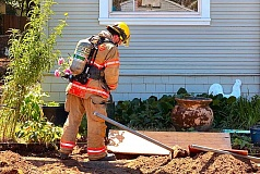DAVID F. ASHTON - With a portable gas leak detector in hand, a firefighter determines the volume of gas escaping from the ruptured pipe on S.E. Henry Street.