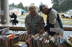 SPOTLIGHT PHOTO: NICOLE THILL - Shirley Palm and Bob Schmore, both of Columbia City, browse through a selection of books during the Columbia City Celebration, Saturday, Sept. 17. Both said they were having a great time at the event despite the wet weather.