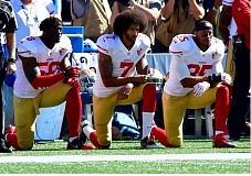 TRIBUNE PHOTO: MICHAEL WORKMAN - San Francisco 49ers quarterback Colin Kaepernick (center) kneels with teammates Eli Harold (left) and Eric Reid during the national anthem Sunday in Seattle.